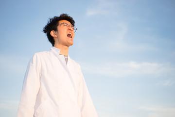 白衣で叫ぶ男性(大声を出す)