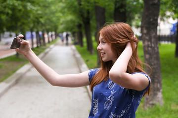 beautiful girl is taking a selfie outdoor