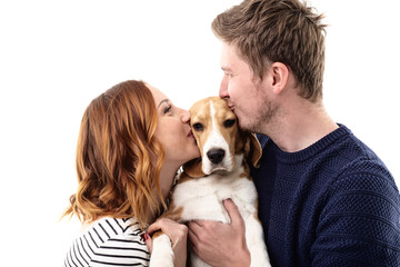 Cheerful married couple kisses their dog