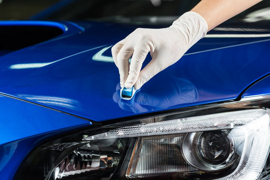 Car detailing series : Closeup of hand coating blue car bonnet