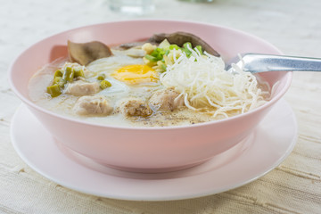 rice porridge, rice gruel or congee with pork, egg, liver,  delicious the traditional Chinese breakfast.