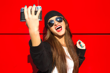 Outdoor fashion closeup portrait of nice pretty young hipster woman posing with camera on the background of red wall on the streets smiling going crazy and showing long tongue