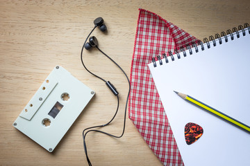 Cassette ,headphones and blank notebook on wood for songwriter b