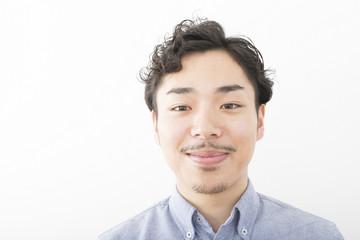 男性 ポートレート 笑み 室内 白バック 髭 パーマ オフィスカジュアル アップ カメラ目線