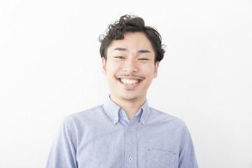 男性 ポートレート 笑う 白い歯 室内 髭 パーマ オフィスカジュアル アップ カメラ目線