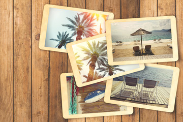 Summer holiday vacation photo album with retro polaroid instant photos on wooden table