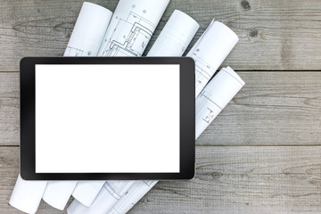 digital tablet with architectural blueprints rolls on wooden bac