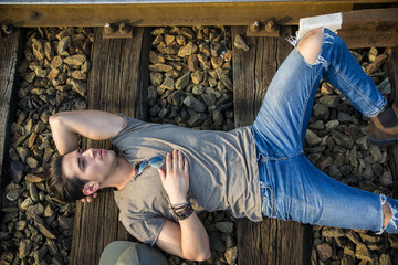 Attractive young man sitting on railroad