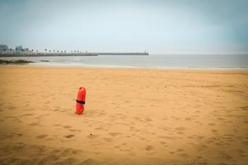 Typical red plastic lifeguard tube on a sandy beach, beach life-saving