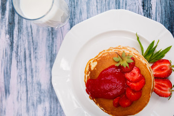 Top view of pancakes with fresh strawberry and jem near glass with milk on white plate on white wooden background.  Stack of pancakes on the table. Copy space.
