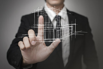 Businessman touching virtual screen a model of the house