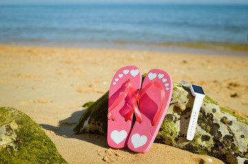 Flipflops and smart watch on sandy ocean beach vacation concept, top view flat lay style