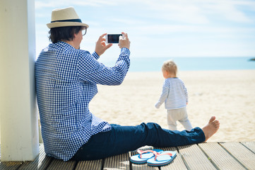 Rear side view of father with smartphone taking picture of baby. beach terrace on sunny day outside