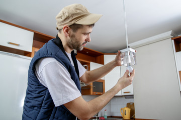 A male electrician fixing light on the ceiling. Worker changing a light bulb in the kitchen. Close-up.