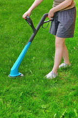 Young White Woman Holding  A Corded Grass Trimmer