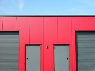 Moderne Lagerhalle mit roter Fassade und grauen Stahltüren und Rolltoren in Lage in Ostwestfalen