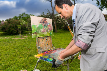 Male contemplative artist cleaning off his palette
