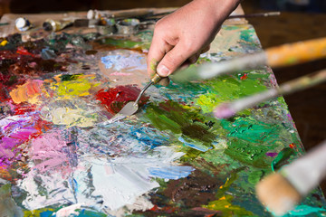 Palette knife in a painter's hand mixing colors