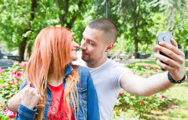 A picture of a happy couple taking selfie in the park