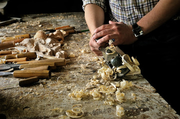 Hands of carver work with jointer in workshop