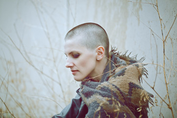 Portrait of sad beautiful Caucasian white young bald girl woman with shaved hair head in leather jacket and scarf shaw looking away, toned with Instagram filters in blue green color