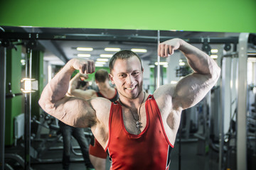 man is engaged in fitness bodybuilder posing shows biceps and smiling