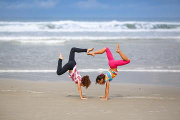 Girls handstanding on the beach