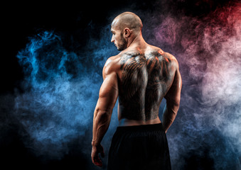 Back view of tattoed muscular man posing. Looking sideways