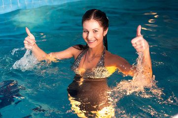 Young beautiful woman shows thumbs up gesture in swimming pool