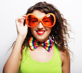 Playful young woman with party glasses.