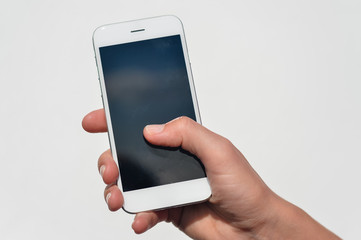 Hand holding smart mobile phone on light wall background, closeup picture