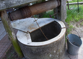 A well with a tin bucket standing beside it