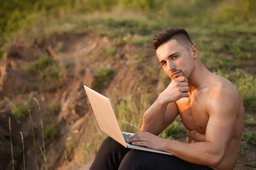 Pensive muscular man with laptop outdoor