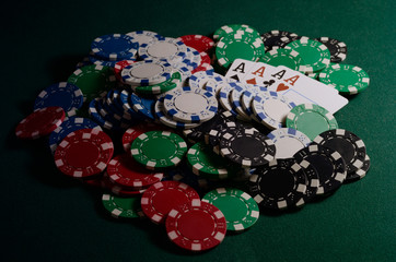 Chips stack and four of kind poker combination on a green background.