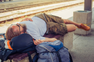 Male backpacker tourist napping on a bench