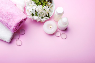 Spa treatment with blooming branch on pink background