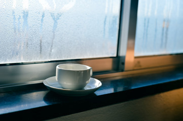 Coffee cup on fogged or frozen background window