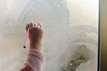 A child hand with pencil drawing picture on fogged or frozen window glass