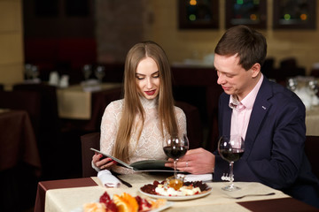 Cheerful couple with menu in a restaurant.