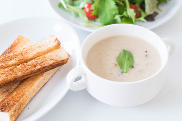 mushroom soup and bread in white ceramic cup