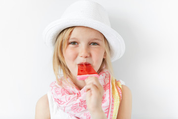 Tiny blond girl in summer hat sucking her sugar candy on stick with enormous pleasure. Bringing joy to little children is a good way to happy family life and friendly relationships.