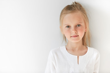 Blond Caucasian female child with green eyes standing quietly indoors and looking straight forward in good and sunny day. White colors make little girl look like a little angel or innocent baby.