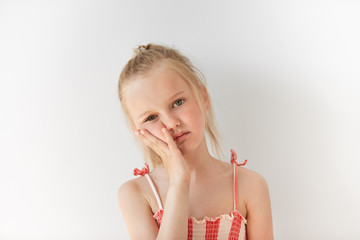 Small Caucasian girl looks tired in morning light indoors. Her facial expression shows boredom and indifference and her face resting on her hand. All her appearance says ?I don't care?.