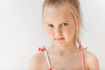Little European girl in summer dress posing on white background. Pretty child with big green eyes and messy blond hair standing with serious facial expression.
