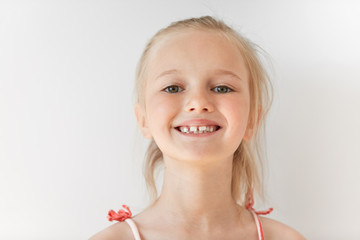 Close-up portrait of blond European little girl smiling with all her teeth. Happy kid in sunny afternoon makes every parent feel good. Childish smile is a source of positive emotions.