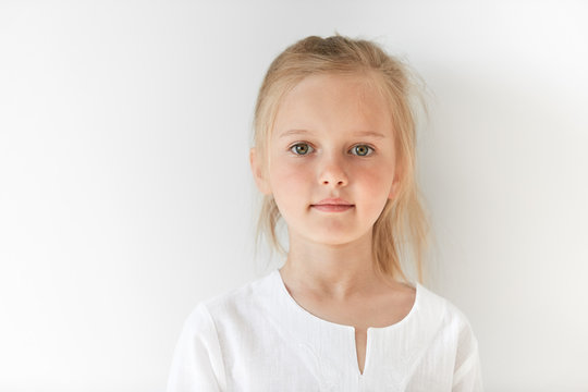 Portrait of angel-like child in white morning light in studio. Little European girl with blond hair looking attractive and balanced showing neutral emotions and radiating tranquility.