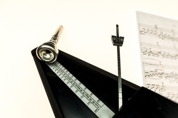 Metronome and mouthpiece of a trumpet isolated on a blank white