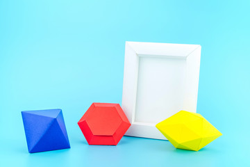 White photo frame(made from paper) and colourful paper jewels on