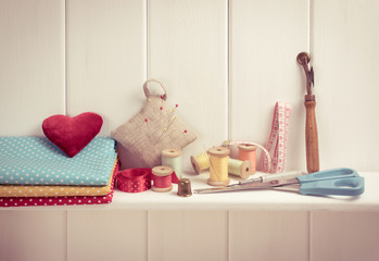 Set of tools for sewing and fabric lying on the wooden shelf. In
