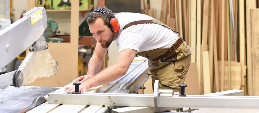 carpenter on a sawing machine // Tischler an einer Sägemaschine in einer Schreinerei